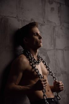 그의 목에 사슬과 함께 젊은 운동 잘생긴 남자. 어두운 배경의 사진