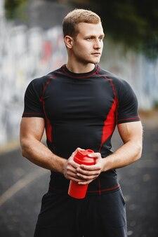 Молодой спортивный человек на стадионе с шейкер в руках парень на вечерней пробежке