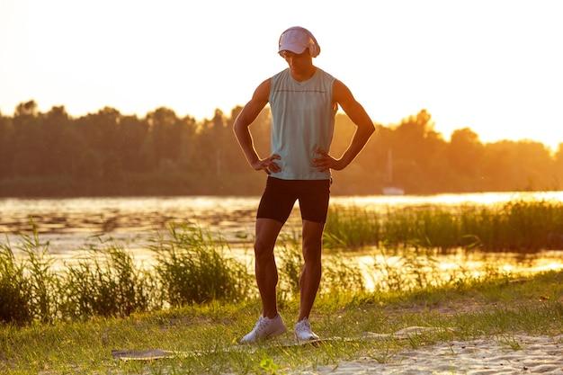 屋外の川沿いで音楽を聴いて運動している若い運動選手