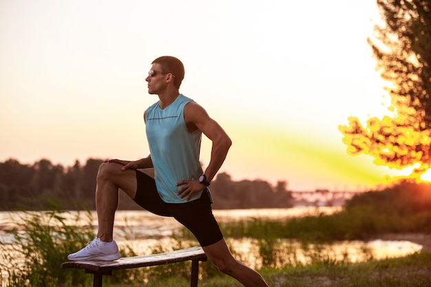 Молодой спортивный мужчина тренируется, слушая музыку на берегу реки на открытом воздухе