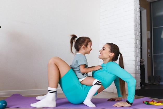 Молодая спортивная мама и девочка вместе делают зарядку дома
