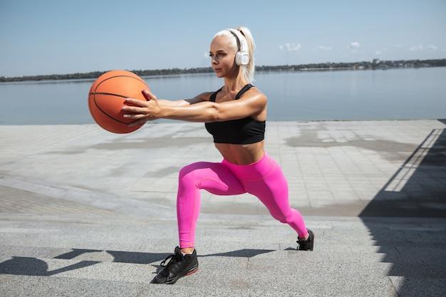 Молодая спортивная женщина в рубашке и белых наушниках, тренирующаяся, слушая музыку на улице на открытом воздухе. выпады с мячом. концепция здорового образа жизни, спорта, активности, похудания.