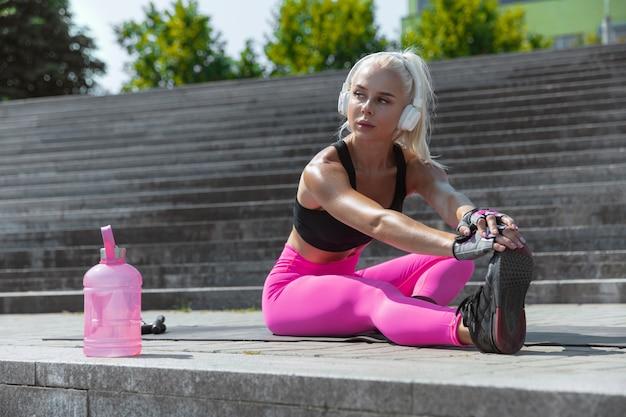 Молодая спортивная женщина в рубашке и белых наушниках работает, слушая музыку на улице на открытом воздухе. делаем упражнения на растяжку. понятие о здоровом образе жизни, спорте, активности, потере веса.
