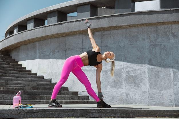 屋外の通りで音楽を聴いて運動しているシャツと白いヘッドフォンの若い運動選手。ストレッチ体操をする。健康的なライフスタイル、スポーツ、活動、減量の概念。