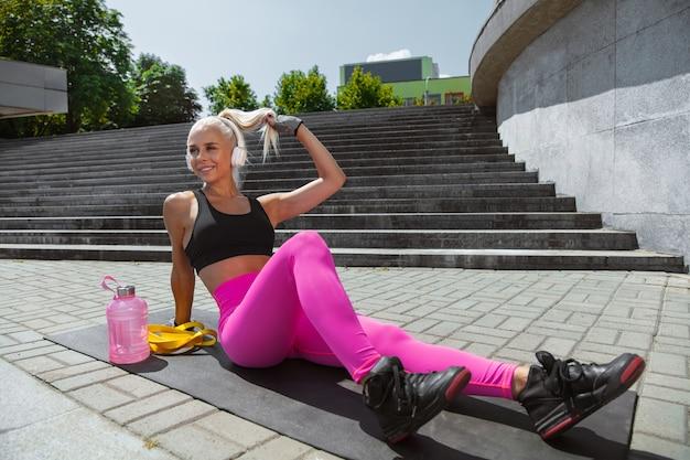屋外の通りで音楽を聴いて運動しているシャツと白いヘッドフォンの若い運動選手。運動後の休息。健康的なライフスタイル、スポーツ、活動、減量の概念。