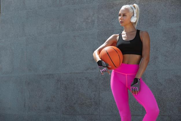 屋外の通りで音楽を聴いて運動しているシャツと白いヘッドフォンの若い運動選手。ボールを持って立っています。健康的なライフスタイル、スポーツ、活動、減量の概念。