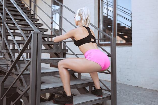 셔츠와 야외 계단에서 음악을 듣고 밖으로 작동하는 흰색 헤드폰에 젊은 체육 여자. 스쿼트와 스텝 수행. 건강한 라이프 스타일, 스포츠, 활동, 체중 감량의 개념.