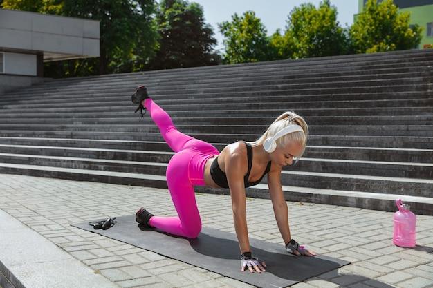 흰색 헤드폰 훈련, 야외 거리에서 음악을 듣고 젊은 체육 여자. 매트 위에서 하체 작업. 건강한 라이프 스타일, 야외 스포츠, 활동, 체중 감량의 개념.