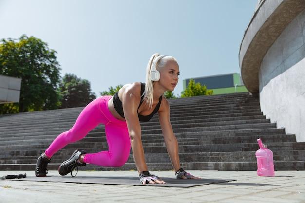 屋外の路上で音楽を聴きながら、白いヘッドフォンのトレーニングをしている若いアスリート女性。下半身をマットの上で動かします。健康的なライフスタイル、野外スポーツ、活動、減量の概念。