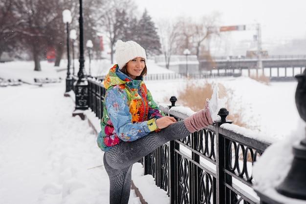 冷ややかな日に走る前に、若い運動女性がウォーミングアップしています。フィットネス、ランニング