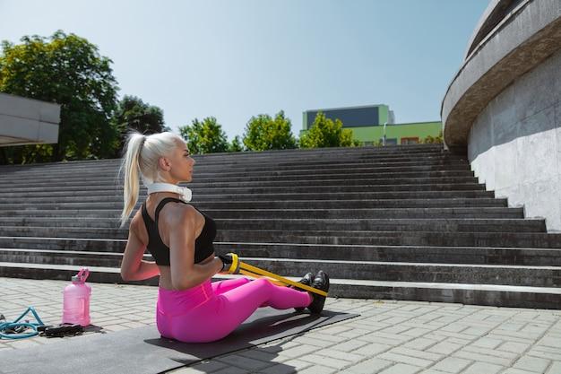 街の通りで運動している若い運動女性