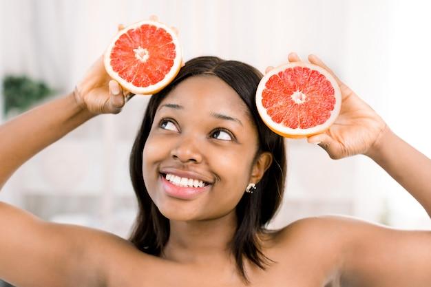 魅力的なアフリカの少女がグレープフルーツの半分を手に持っています。スキンケアのコンセプトです。