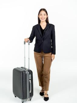 出張で彼女の黒いスーツケースを運び、笑顔でカメラを見てスーツを着た若い魅力的なアジアの実業家