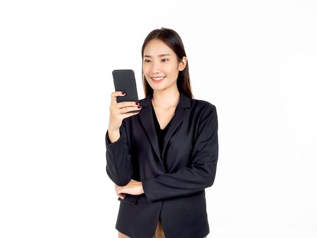 画面を見ながら、スマートフォンを使用してスーツを着た若い魅力的なアジアの実業家