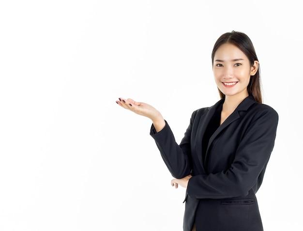 복사 공간에 그녀의 손으로 뭔가를 제시하고 카메라를 찾고 검은 양복에 젊은 매력적인 아시아 경제인