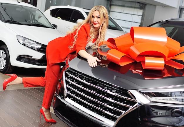 Молодая привлекательная блондинка в красном костюме обнимает большой черный кроссовер с огромным красным бантом на поверхности автосалона или автосалона.