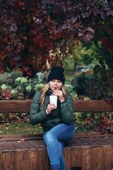 黒い帽子、ブルージーンズ、緑のジャケットのウェーブのかかった髪を持つ若い魅力的なブロンドの女性は、公園のベンチ、明るく美しい秋の風景に座ってコーヒーを飲みます