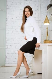 Молодая привлекательная брюнетка в белом джемпере и черной юбке опирается на край стола в ... Premium Фотографии