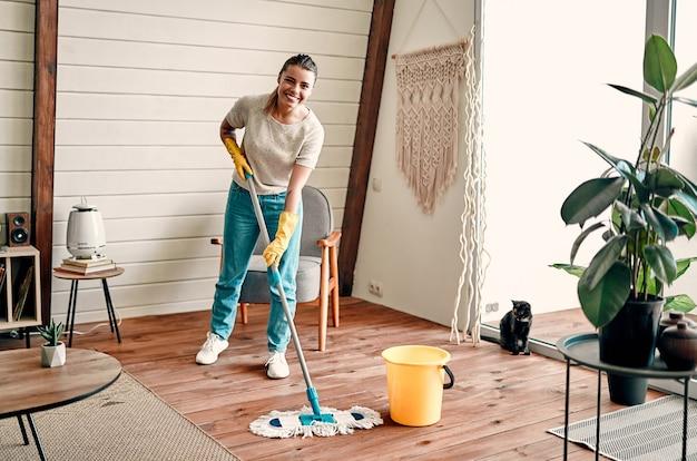 Молодая привлекательная девушка в резиновых перчатках и наушниках слушает музыку и моет деревянный пол в своей комнате. генеральная уборка дома.