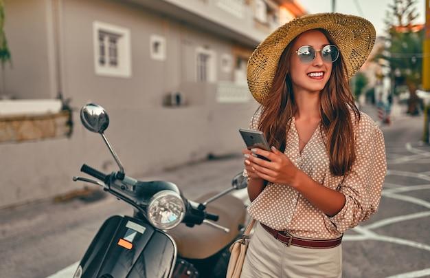 선글라스와 그녀의 손에 전화가 달린 밀짚 모자에 젊은 매력적인 소녀가 도시 거리의 스쿠터 근처에 서 있습니다. 여행, 관광 개념.