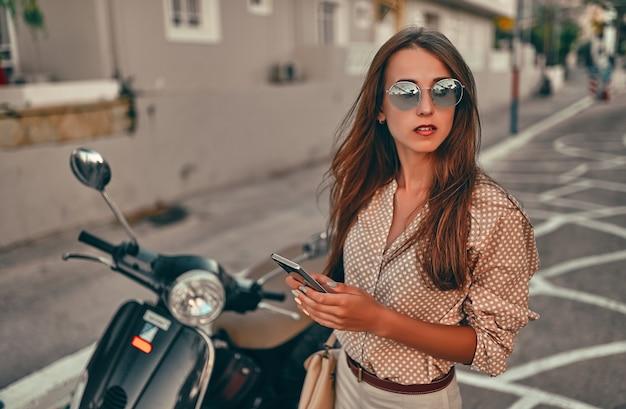 그녀의 손에 전화와 선글라스에 젊은 매력적인 여자는 도시 거리에 스쿠터 근처에 서있다. 여행, 관광 개념.