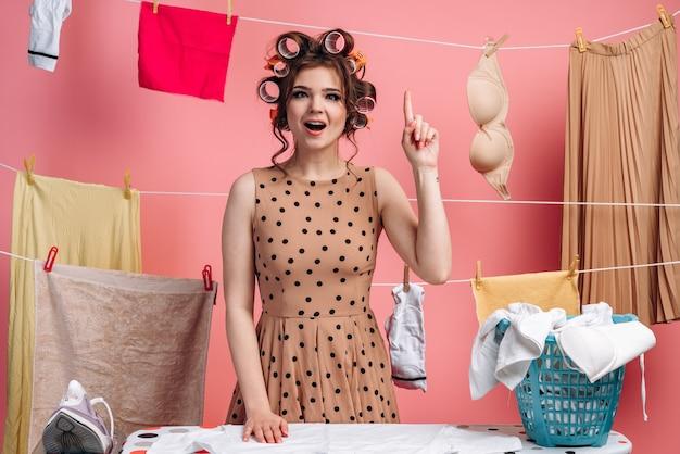 폴카 도트 드레스를 입은 젊고 매력적인 주부가 집게 손가락을 들어 올려 좋은 생각을 가지고 있습니다.