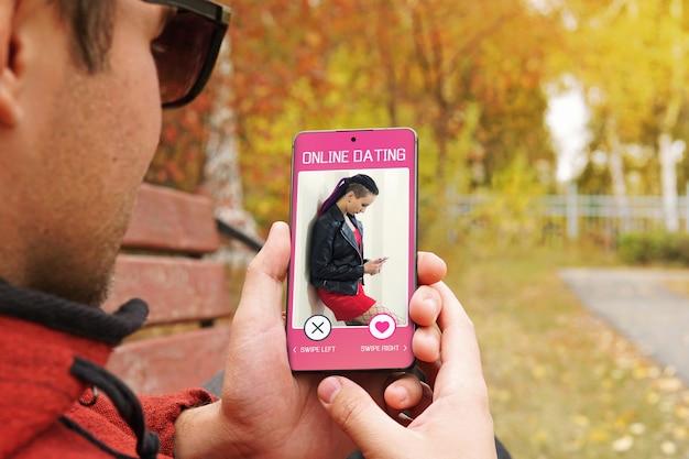 매력적인 젊은 남자가 온라인 데이트 앱에서 커플을 찾고 있습니다. 인터넷에서 사랑을 검색하십시오. 모든 화면 그래픽이 구성되어 있습니다.