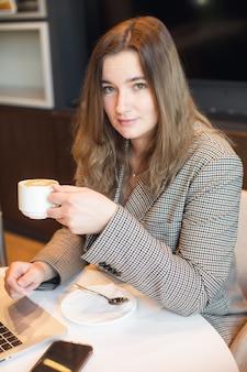 Молодая привлекательная пухлая девушка сидит в кафе, пьет кофе и работает на ноутбуке, фото высокого качества