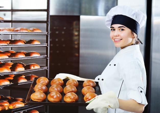 흰색 요리사의 재킷과 모자에 젊은 매력적인 여자 베이커