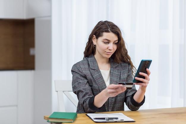 Молодая привлекательная женщина вводит данные своей кредитной карты через приложение на телефоне, делая покупки в интернете