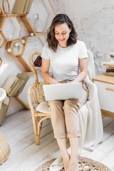 Молодая привлекательная женщина в яркой современной квартире использует ноутбук для общения или изучения фотографий высокого качества онлайн.