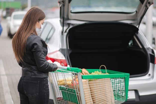 트롤리에서 자동차 트럭으로 슈퍼마켓에서 식료품을 복용하는 젊은 매력적인 여자