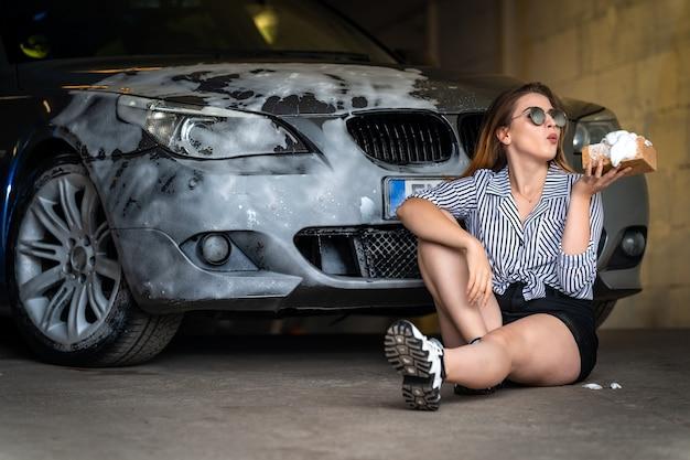 若い魅力的な女性は、スポンジと泡で車を洗います。