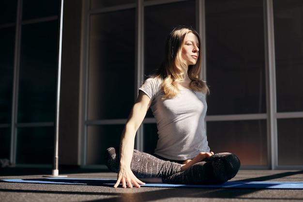 明るい髪の若い魅力的な女性がヨガを練習しています。ヨガ、フィットネス、健康的なライフスタイル
