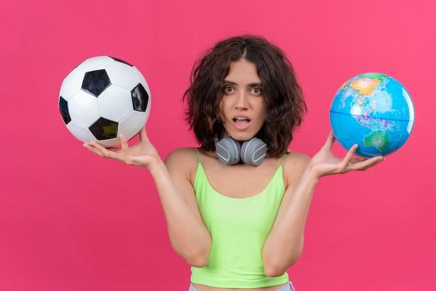 Молодая привлекательная женщина с короткими волосами в зеленом топе в наушниках держит глобус и футбольный мяч