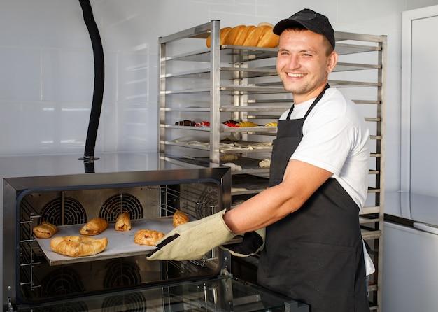젊은 제빵사가 제과점의 오븐에서 페이스트리를 꺼냅니다.