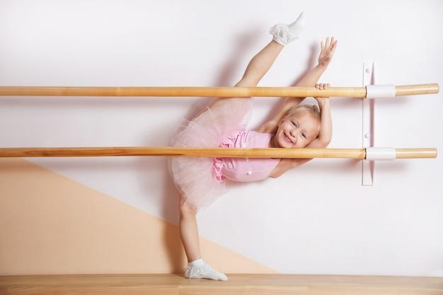 분홍색 드레스를 입은 어린 발레리나 소녀가 발레 스튜디오에 종사하고 있다