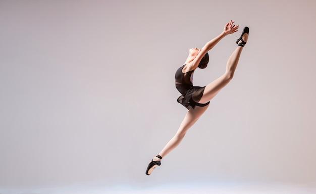 Юная балерина в черном купальнике и пуантах прыгает на ярком фоне.