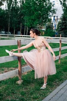 Юная балерина в розовом платье делает упражнения на растяжку в парке с зеленой травой и деревьями в ...