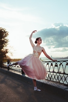Юная балерина в розовом шелковом платье танцует и выполняет упражнения, держась за кастиронный забор ...