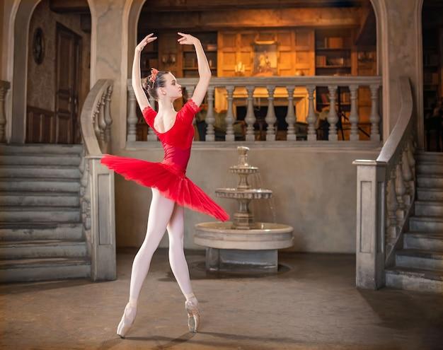 빨간 투투를 입은 젊은 발레리나가 궁전의 연극 적 풍경에서 춤을 추고 있습니다.