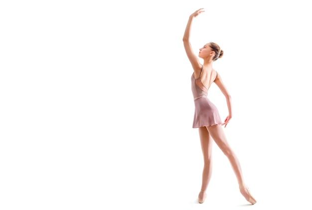 Молодая балерина в пуантах позирует в изящной позе на белом фоне
