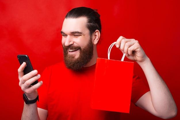 若いビーズの男が赤い壁の近くで彼の携帯電話からオンラインショッピングをしています