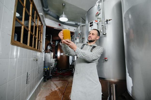 若いひげを生やした醸造者は、醸造所で淹れたてのビールの品質管理を行っています。