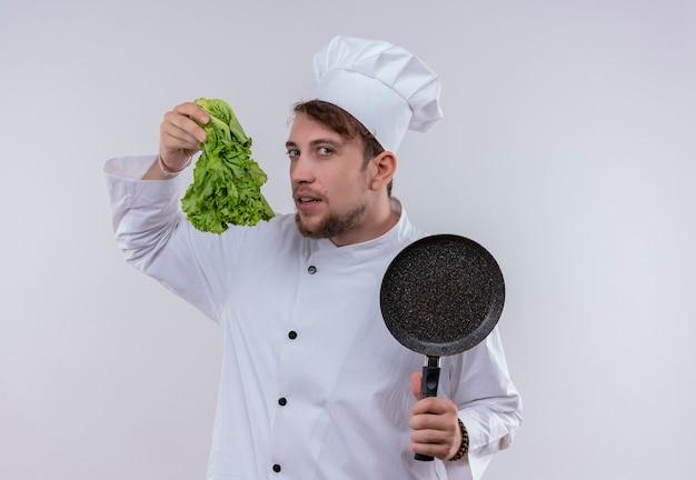 白い壁を見ながらフライパンと緑のレタスを保持している白い制服を着た若いひげを生やしたシェフの男