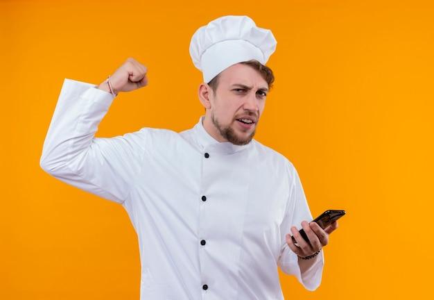 흰색 제복을 입은 젊은 수염 난 요리사 남자가 주먹을 움켜 쥐고 오렌지 벽을 보면서 휴대 전화를 들고