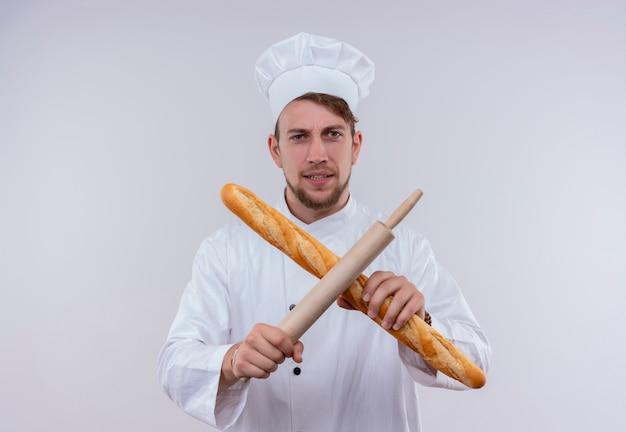 白い壁を見ながら、x記号で麺棒でバゲットパンを保持している白い炊飯器の制服と帽子を身に着けている若いひげを生やしたシェフの男