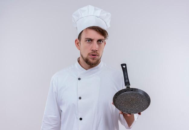 흰 벽에 심각한 표정으로 보면서 흰색 밥솥 유니폼과 모자를 들고 프라이팬을 입고 젊은 수염 난 요리사 남자