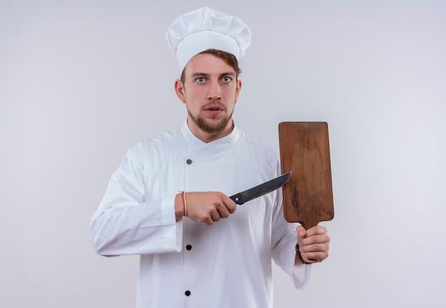 白い壁を見ながらナイフで木製のキッチンボードを指している白い炊飯器の制服と帽子を身に着けている若いひげを生やしたシェフの男