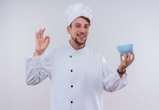 白い壁を見ながら彼の手に青いボウルと指でおいしいokサインを示す白い炊飯器の制服と帽子を身に着けている若いひげを生やしたシェフの男